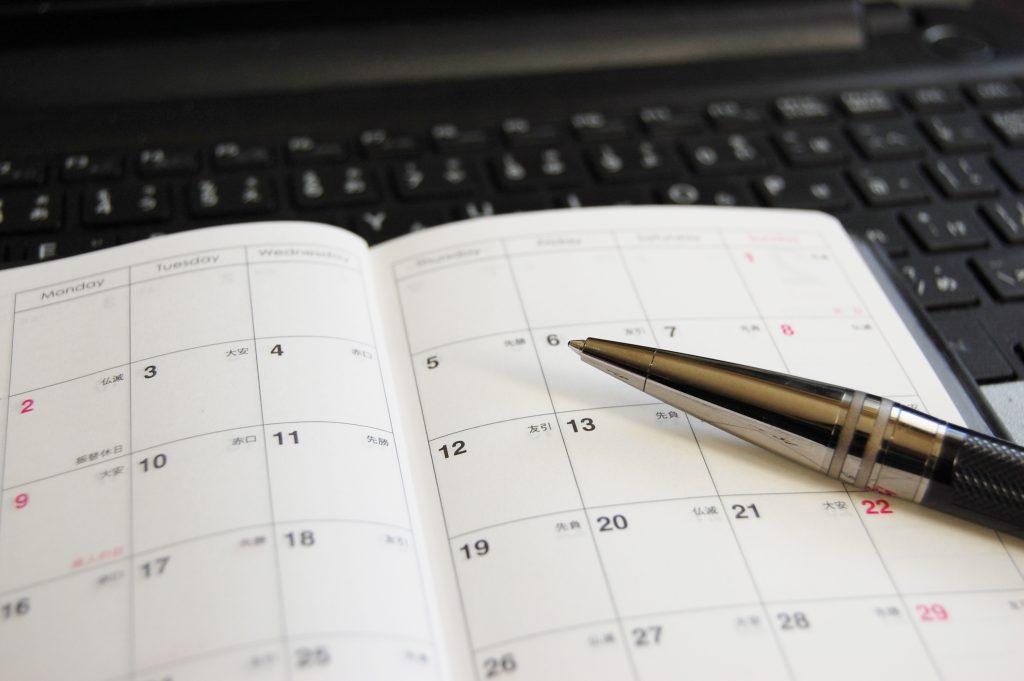 スケジュール帳とボールペンの写真