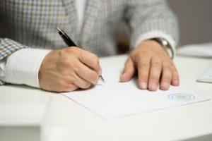 保険担当が紙に文字を書いている様子