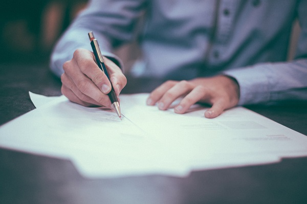 書類を書いている男性の手