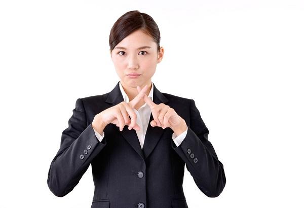 指でバツを作る女性の写真