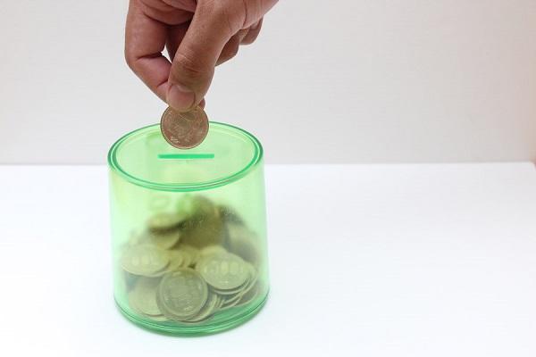 小銭を貯金箱に入れる写真