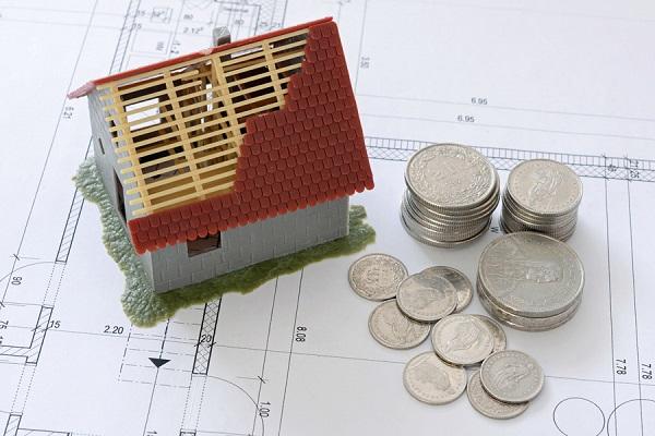 壊れた家の模型と小銭の写真