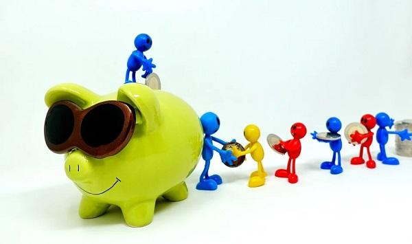 豚の貯金箱に小銭を入れている写真